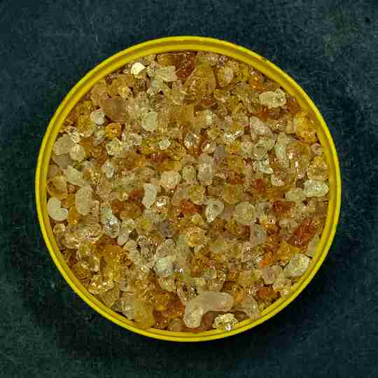 bowl of yellow sun fiber crystals with a dark background