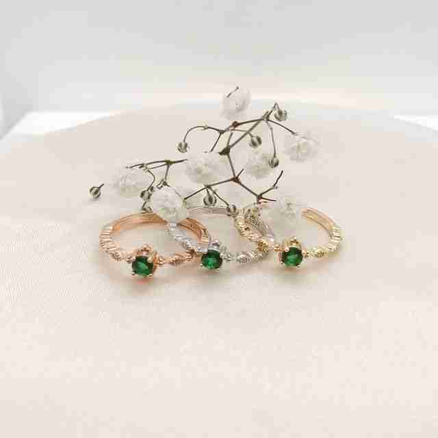 Three green garen rings in rose gold vermeil, yellow gold vermeil, and sterling silver