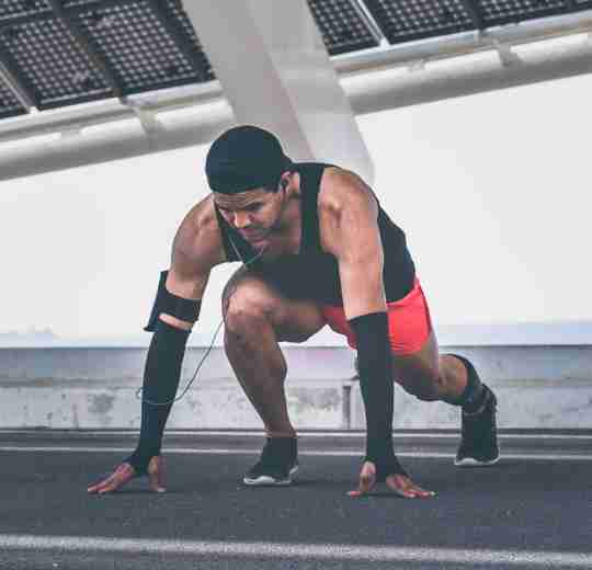 A male athlete stretching after taking carnitine with Cardio Surge Energy to reduce muscle damage.
