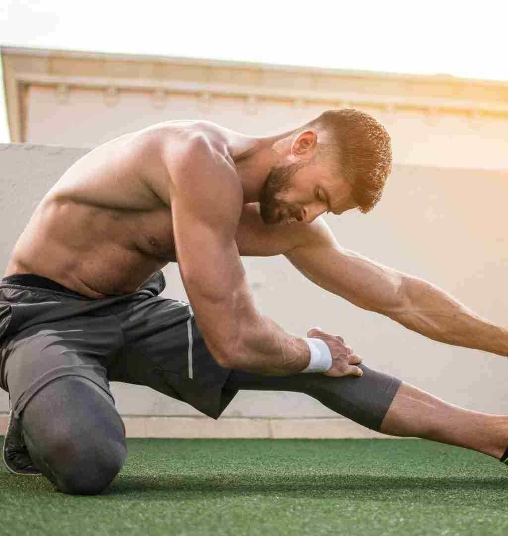 Male fitness athlete stretching in the morning on turf.