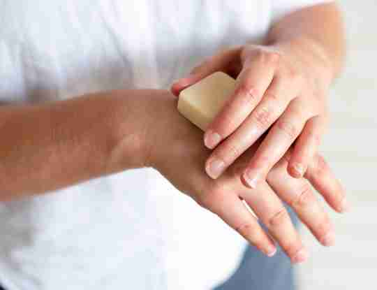 hands holding beesilk hard lotion bar