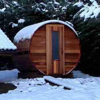 Image of a barrel sauna, which is an outdoor home sauna, in the snow
