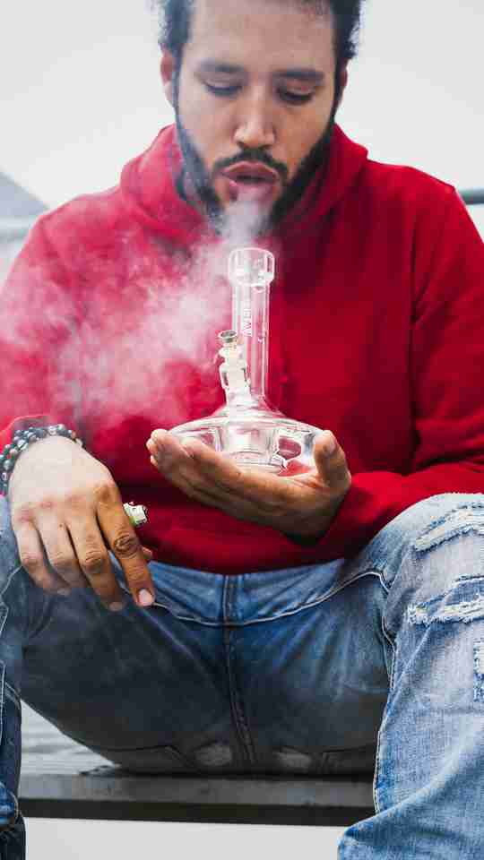 man in red smoking from a dab rig