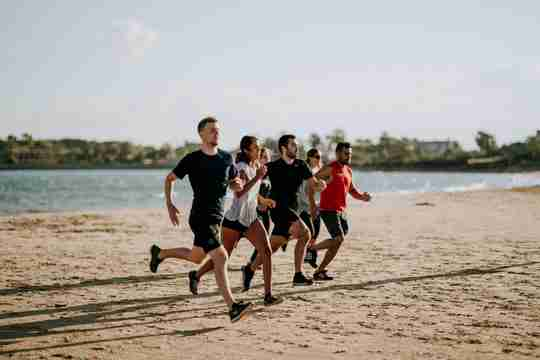 A group of guys running on the beach