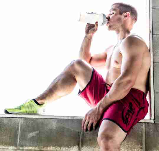 Male CrossFit athlete drinking a whey protein shake after his workout.