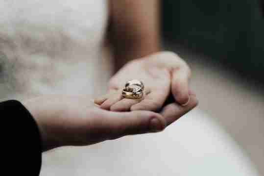 A couple holding wedding bands
