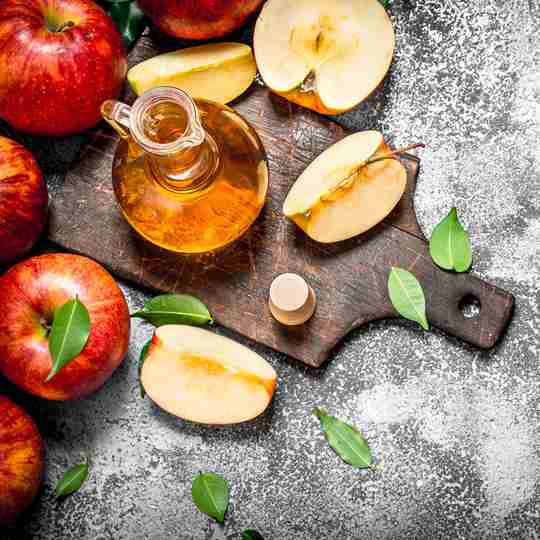 Great background with wood cutting board, apples, leaves and apple cider vinegar