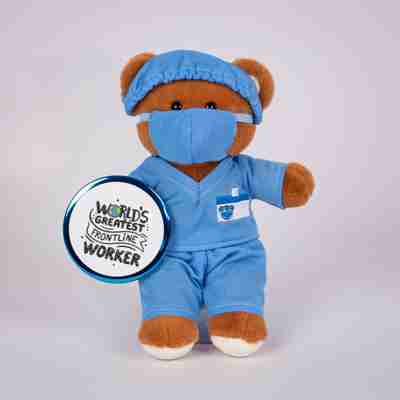 Standing brown bear wearing doctors scrubs and cap holding a button