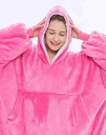 Female is in her Marshmallow Happy Place in a hot pink super cosy The Marshmallow blanket hoodie