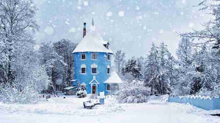 winter scene with a blue round house with snow falling