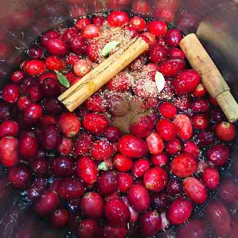 cranberries cooking in a pot with spices