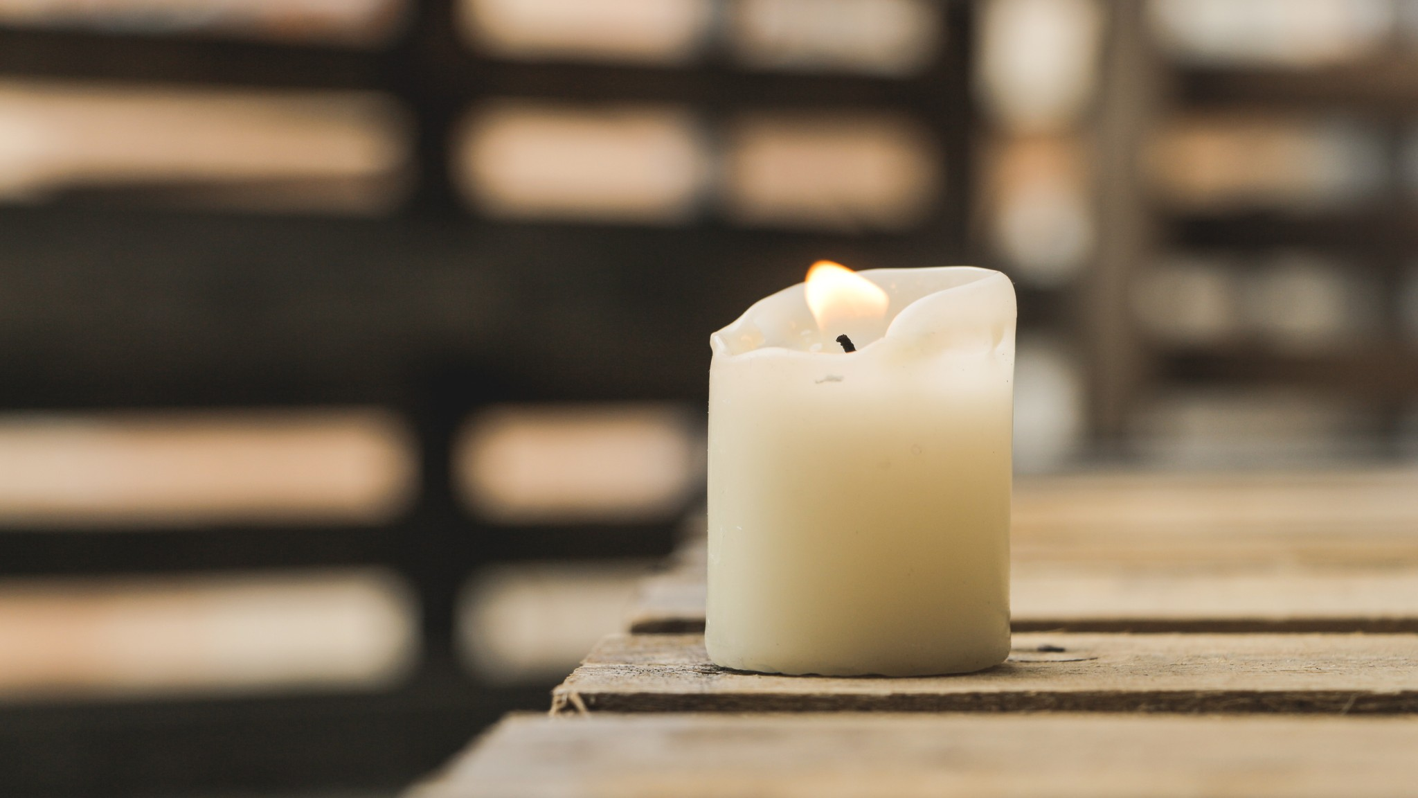 white lit pillar candle sits on wooden boards with blurred background