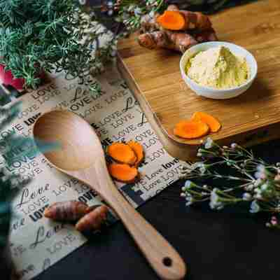 wood spoon and cutting board with green herbs and turmeric