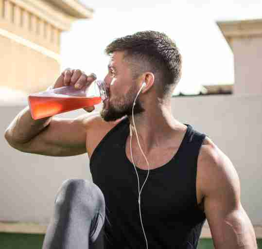 Male fitness athlete drinking a drink while exercising.