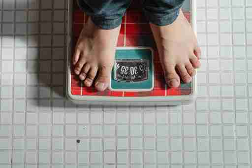 person weighing themself weightloss bathroom scale
