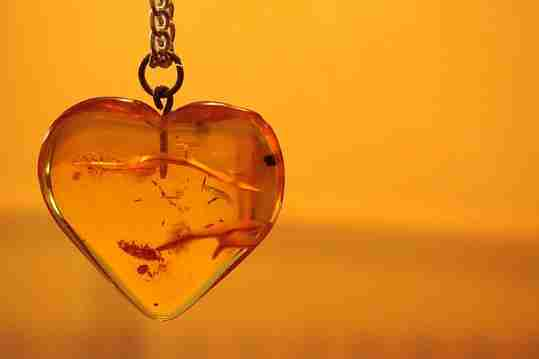 A heart-shaped amber pendant with artifacts