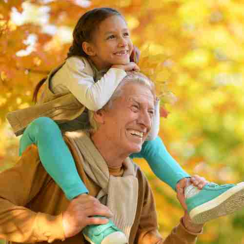 Grandad With Grand-daughter Having Shoulder Ride In Park