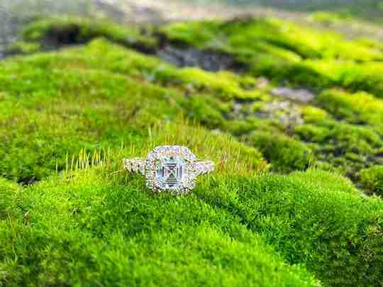 A Ritani diamond ring sitting on green grass