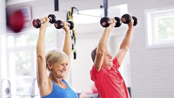 Couple Two People Exercising Lifting Weights in Gym