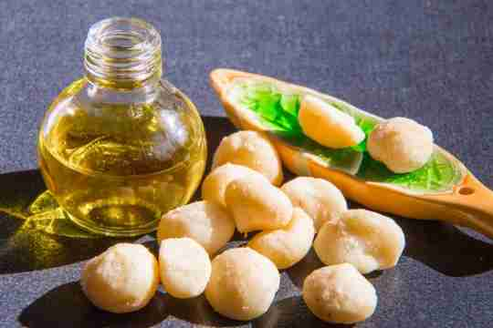 macadamia nut oil with macadamia nuts and spoon