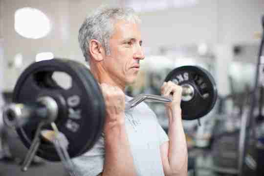 Older Fit Man Lifting Weights Exercising in Gym