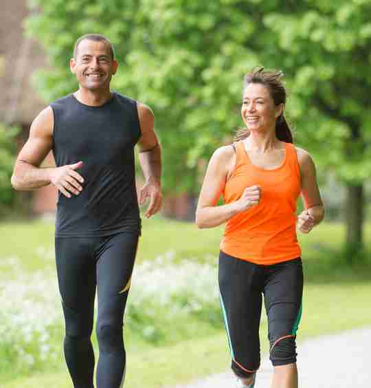 Happy fit couple jogging in the park