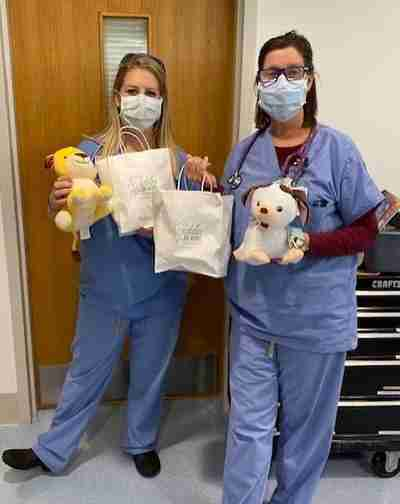 Two nurses holding teddy bears and a gift bag