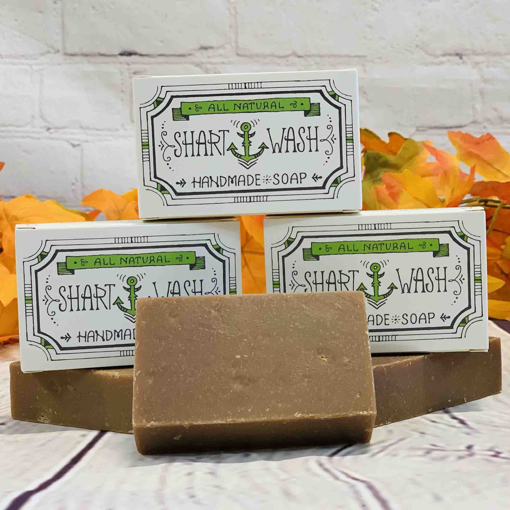picture of 3 brown bars of Pumpkin Spice Latte scent shart wash handmade soap on a wood background with orange and yellow autumn leaves and a pinecone