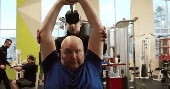 Men Exercising in Gym Man Helping Another Man Lift Weight