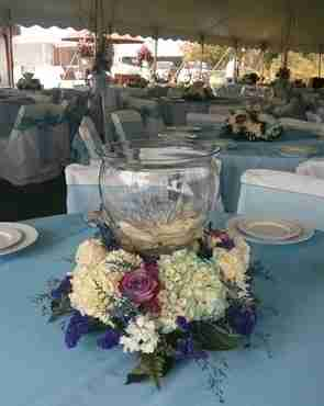 A glass centerpiece decorated with flowers at the bottom