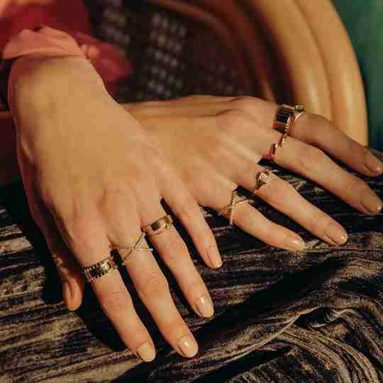 A model wearing multiple gold rings