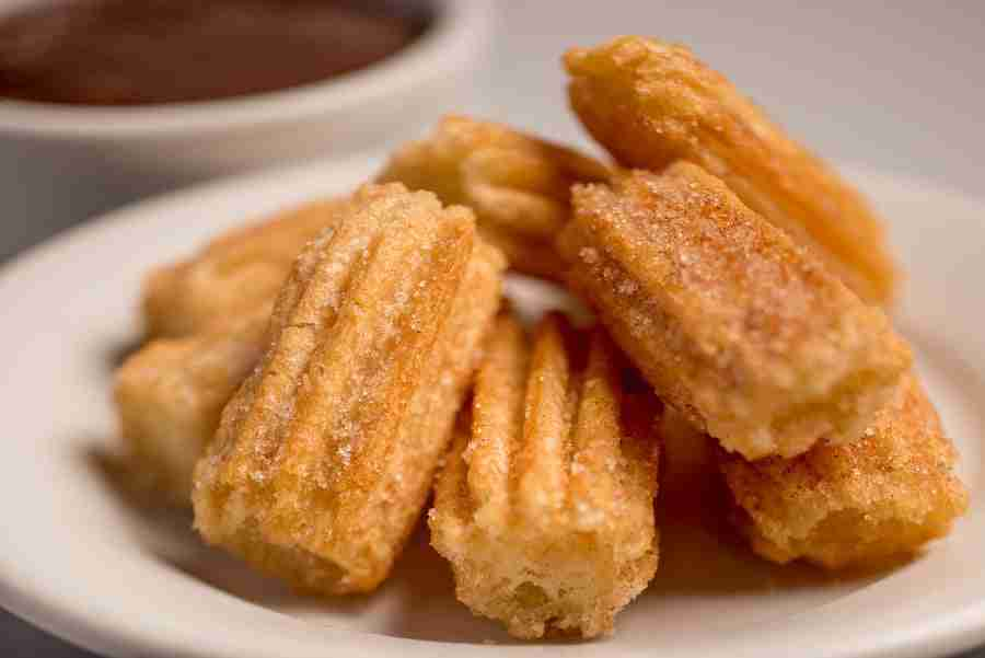 A photo of Disney churros on a white plate - yum! Photo by Popsugar