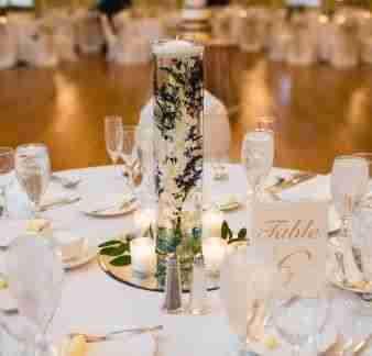A tall glass centerpiece filled with flower stems