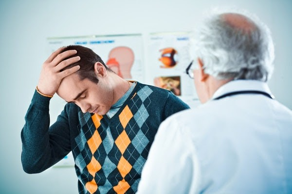 Man Holding Head In Front of Doctor