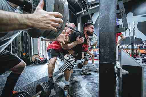 man lifting weights barbell squat pr