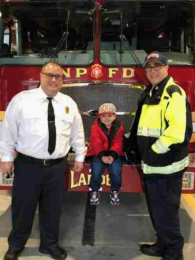 Two fireman standing in between a little boy sitting on a fire truck