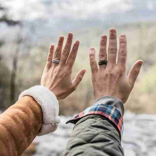 A couple outdoors wearing QALO rings