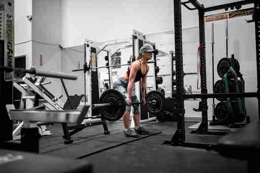 woman lifting weights barbell weights room