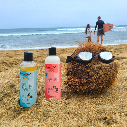 Burrows Best Hair & Body Wash and Lotion sit on the beach next to a brown coconut wearing Frogglez adult swim goggles. Surfers stand on the edge of the ocean in the background.