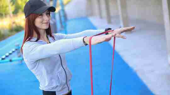 Woman using resistance bands outside