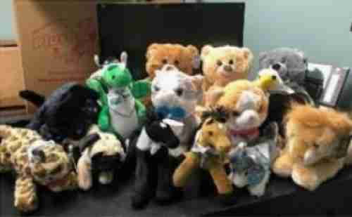 A variety of plush animals wearing a bandana
