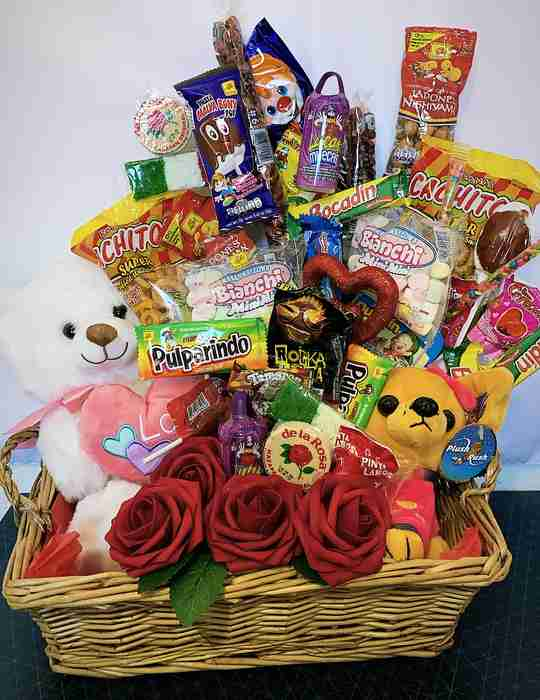 A basket filled with candy, plush toys, and roses