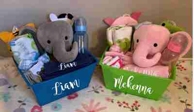A boy and a girl customized gift basket filled with a pink or gray elephant, and baby accessories