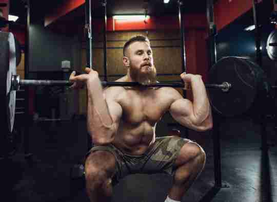 A male athlete show the best practices for squatting everyday.
