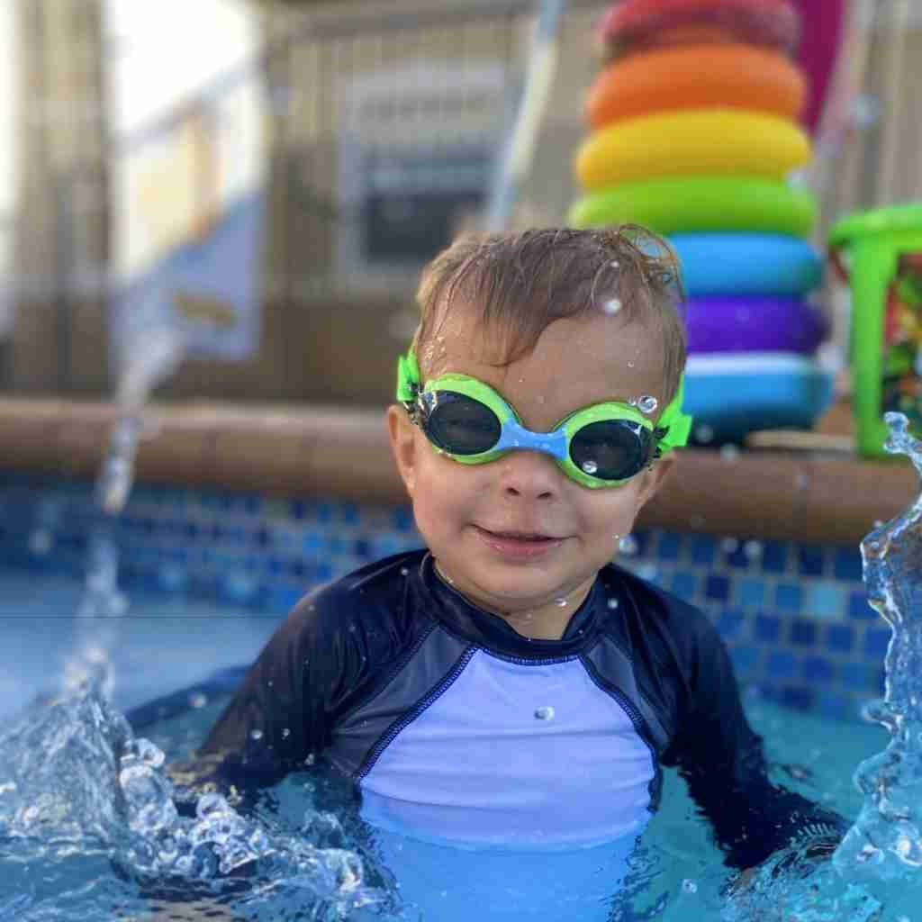 Boy swimming underwater wearing blue Frogglez swim goggles in blue water with bubbles rising