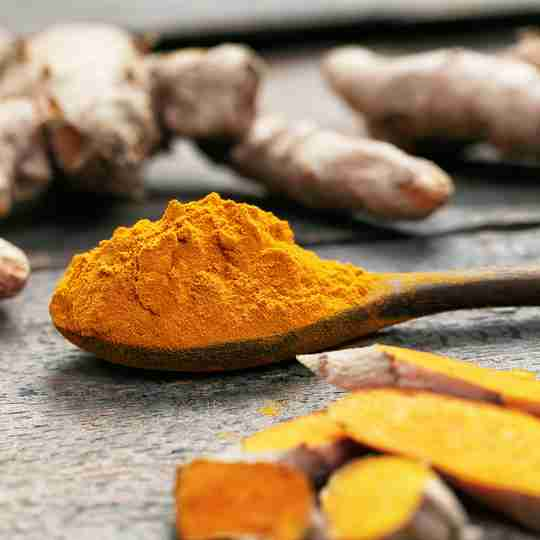 Turmeric powder with wooden spoon and turmeric roots