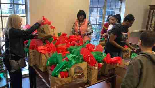 Volunteers sorting through gift bags.