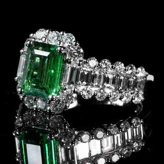 Emerald ring with diamond-encrusted band and halo