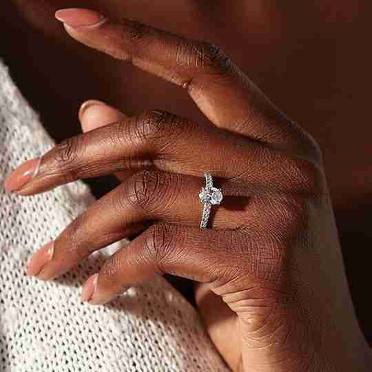A woman wearing a diamond engagement ring from Blue Nile