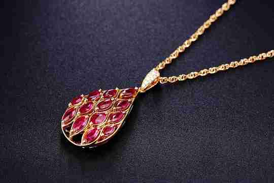 A gold necklace with a ruby pendant